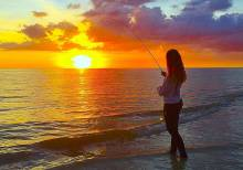 Woman fishing on the beach at sunset