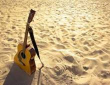 Guitar sitting in sand