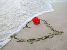 Heart in sand being washed away by small wave