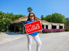 """Woman holding red """"sorry were closed"""" sign."""
